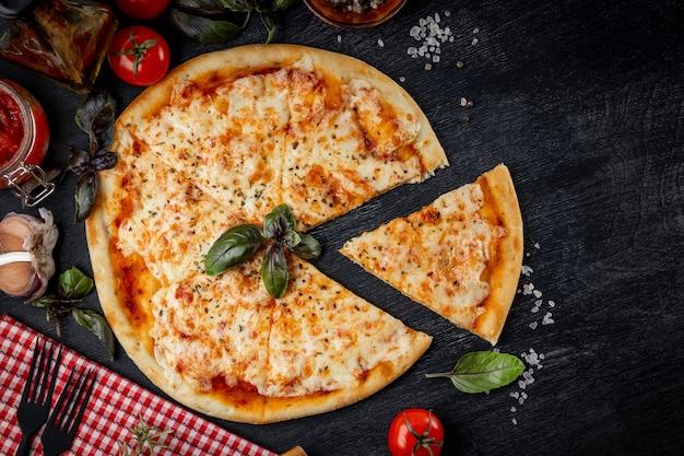 Pizza italiana margarita tagliata a pezzi e ingredienti per la sua preparazione sul tavolo in vista