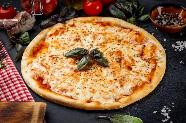 Pizza italiana margarita e ingredienti per la sua preparazione sul primo piano del tavolo.