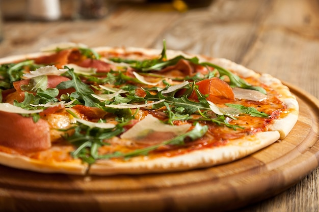 La pizza italiana parma giace su un bellissimo tavolo di legno