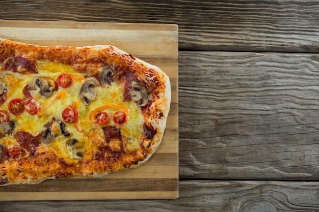 La pizza italiana è servita sul tagliere su una tavola di legno