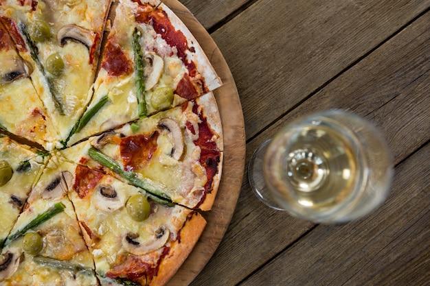 Pizza italiana servita su un vassoio con un bicchiere di vino
