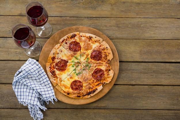 Pizza italiana servita in un vassoio per pizza con vino rosso