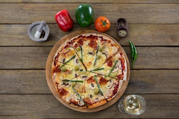 Pizza italiana servita in un vassoio per pizza con una bottiglia di vino