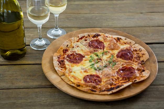 Pizza italiana servita in un vassoio per pizza con bicchieri di vino