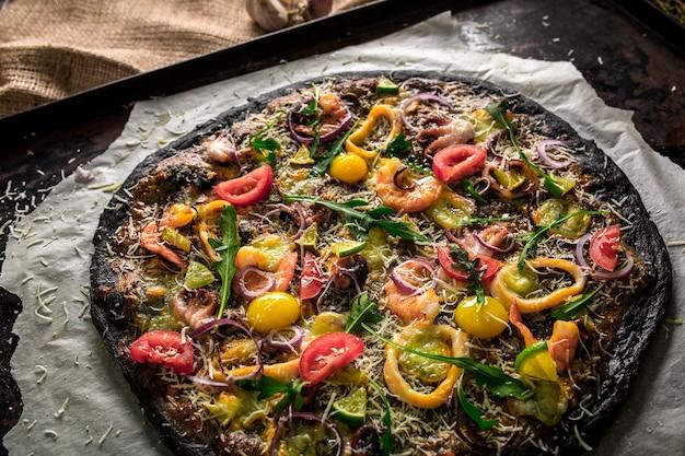 Pizza italiana con pasta nera e frutti di mare su una teglia da forno. sopra adagiare calamari, gamberi, polpi, cipolle, pomodori. nero di seppia