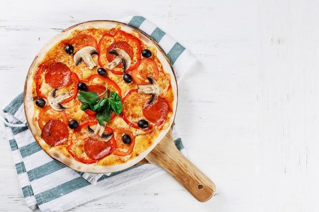 Pizza italiana con funghi, basilico, pomodoro, olive e formaggio