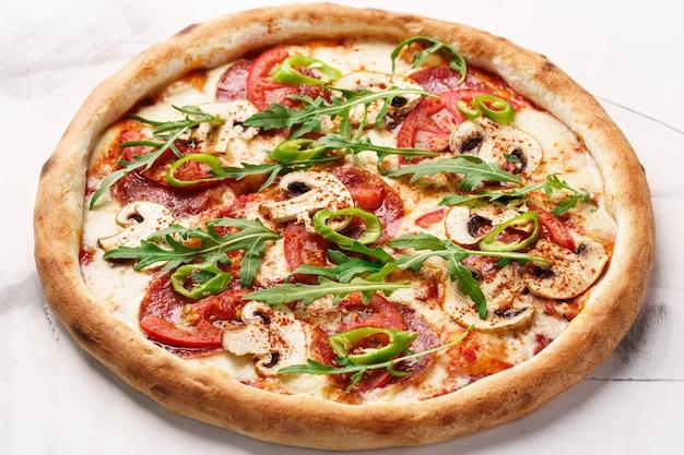 Pizza italiana con funghi salame pomodori formaggio spezie rucola e peperoncino