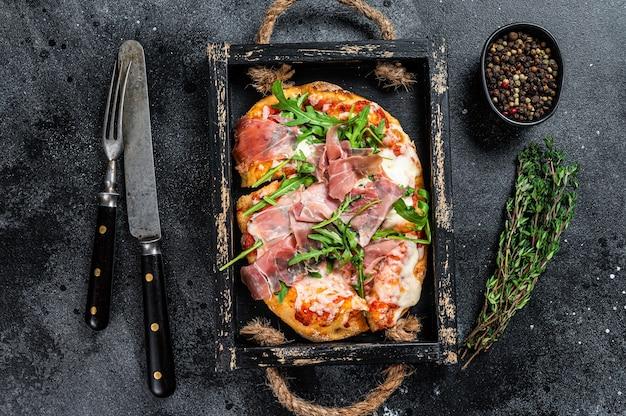 Pizza italiana con prosciutto di parma, insalata di rucola e formaggio in un vassoio di legno rustico