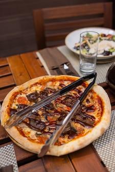 Pizza italiana con prosciutto pomodori olive olio d'oliva parmigiano e rucola. sfocato sfondo colorato girato in studio.