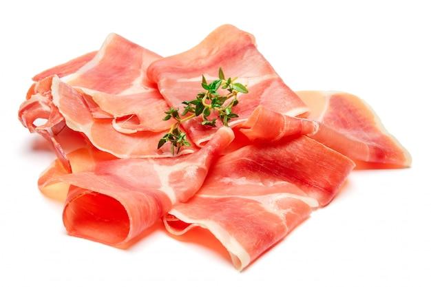Prosciutto crudo italiano o jamon spagnolo. prosciutto crudo su superficie bianca