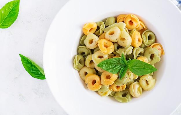 Pasta italiana dei ravioli con spinaci e ricotta nel piatto bianco. pasta italiana dei tortellini. vista dall'alto, piatto, sopraelevato