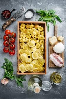 Ravioli fatti a mano crudo italiano con ingredienti freschi, basilico, pesto, prosciutto, mozzarella, set di parmigiano, in una scatola di legno, sul tavolo grigio, vista dall'alto laici piatta
