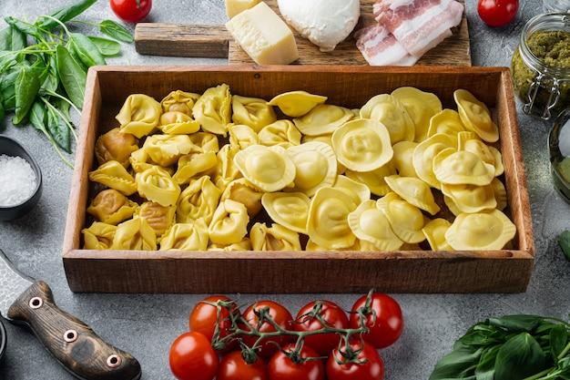 Crudo italiano ravioli fatti a mano con ingredienti freschi, basilico, pesto, prosciutto, mozzarella, parmigiano, in una scatola di legno, sul tavolo grigio