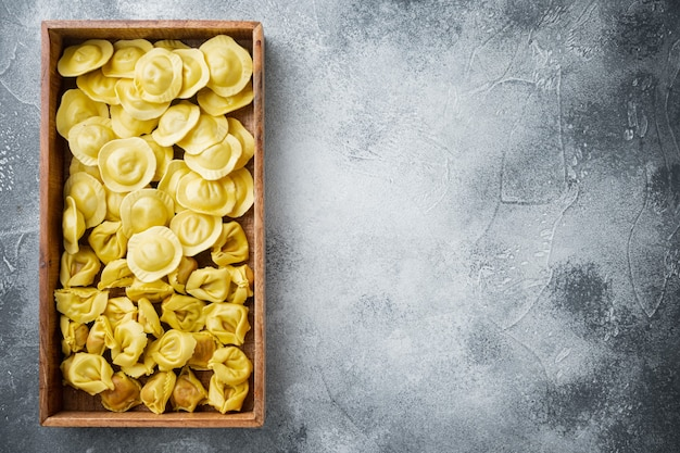 Set di tortellini e ravioli fatti a mano crudo italiano, in una scatola di legno, sul tavolo grigio, vista dall'alto laici piatta