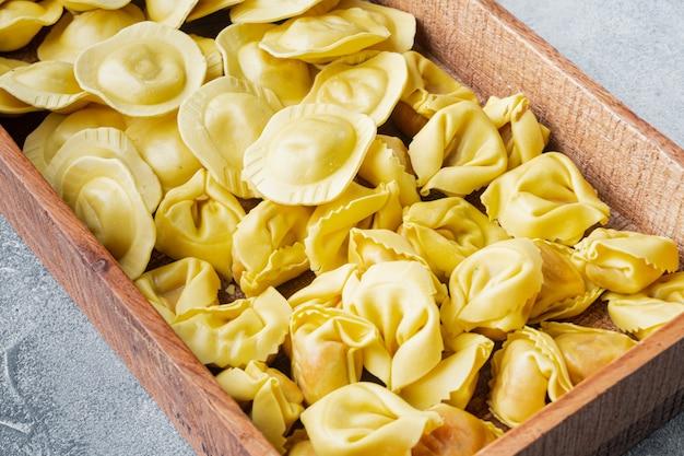Servizio di tortellini e ravioli crudi italiani fatti a mano, in scatola di legno, su tavola grigia
