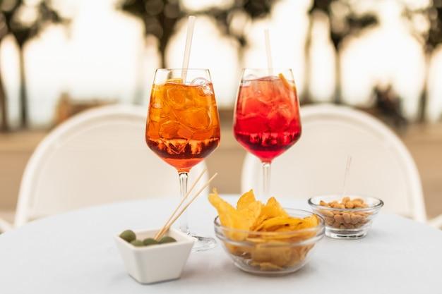 Cocktail rinfrescanti italiani con snack sul tavolo in una sera d'estate.