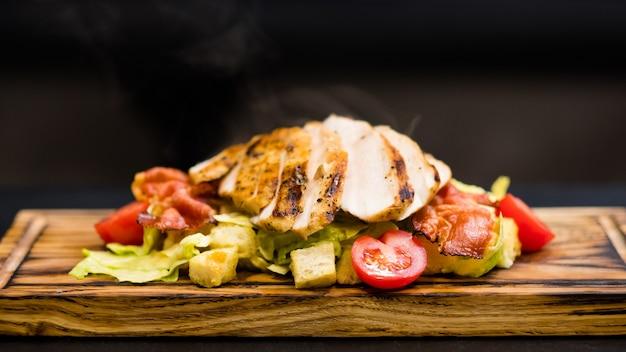 Menù ristorante italiano. primo piano di insalata caesar con filetto di pollo affumicato, patatine di pancetta e verdure su tavola di legno.