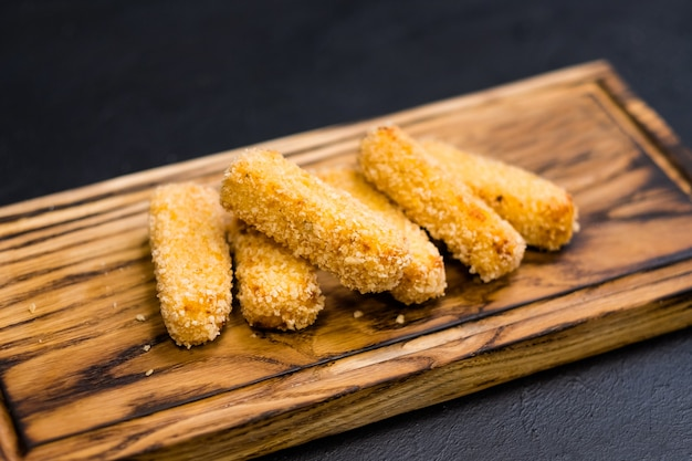 Menù ristorante italiano. patatine fritte di polenta nel pangrattato panko su tavola di legno.