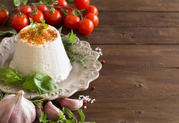 Ricotta italiana, verdure ed erbe aromatiche su un tavolo di legno si chiuda