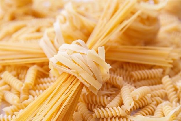 Tagliatelle crude arrotolate italiane e pasta degli spaghetti