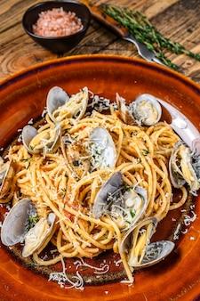 Pesce italiano spaghetti alle vongole in un piatto rustico. fondo in legno. vista dall'alto.