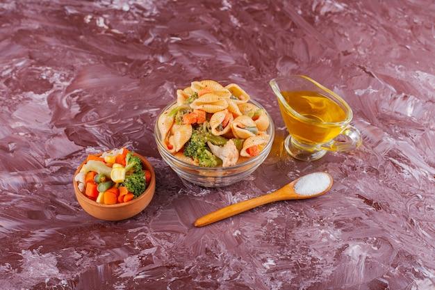 Pasta italiana delle coperture con olio e insalata mista di verdure sul tavolo luminoso.