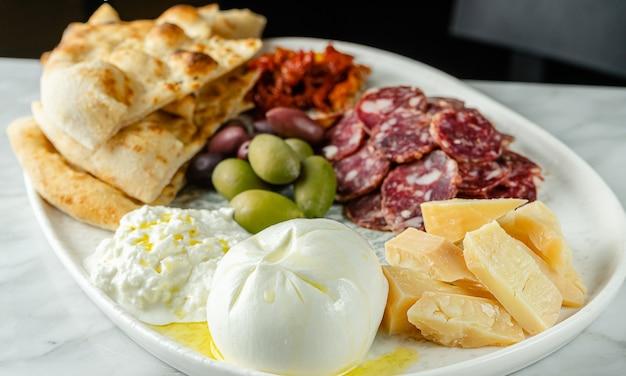 Spuntini italiani o piatto di antipasti con diversi formaggi, carne e focacce