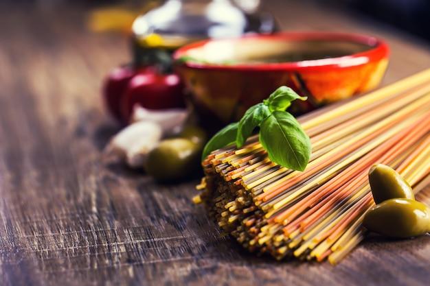 Concetto di spaghetti italiani serviti con succose olive verdi, pomodori, olio d'oliva e basilico aromatico. il tutto adagiato sulla scrivania in legno rustico.