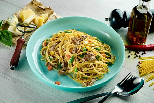 Spaghetti italiani con salsa bianca, carne di manzo, verdure e parmigiano serviti in un piatto blu su un tavolo di legno. cibo del ristorante.