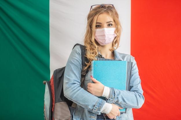 Studente italiano tiene in mano un libro di testo, indossa zaino e maschera facciale.