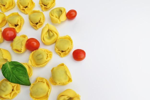 Pasta italiana ripiena, tortellini, ravioli con pomodorini. gustosi ravioli crudi con pomodorini e basilico su fondo chiaro. il processo di produzione dei tortellini italiani ,. copia spazio.