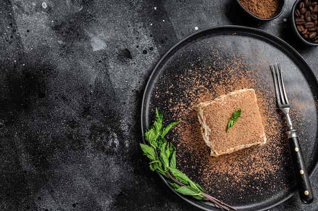 Torta tiramisù italiana con cacao e menta su un piatto. sfondo nero. vista dall'alto. copia spazio.