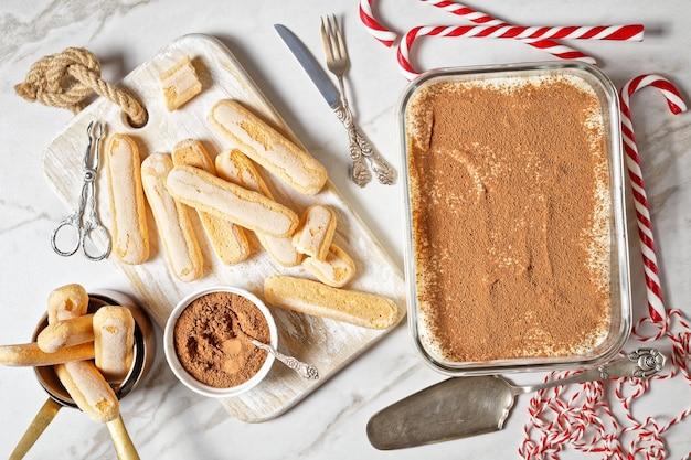 Tiramisù italiano di savoiardi, caffè espresso e mascarpone servito su un contenitore di vetro con ingredienti su uno sfondo di marmo bianco con caramelle di canna da zucchero di natale, vista dall'alto, primo piano