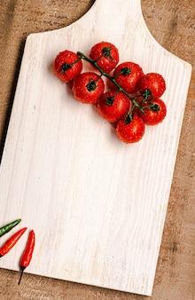 Pomodori italiani su una tavola di legno bianca con fondo rustico in legno marrone e peperoni intorno top...