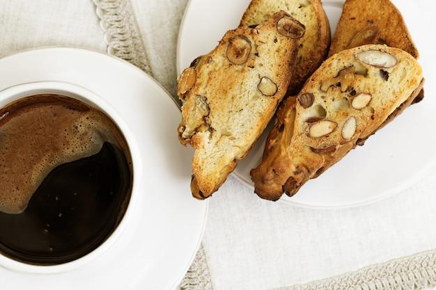 Biscotti tradizionali italiani con i dadi sul piatto bianco sul tavolo.