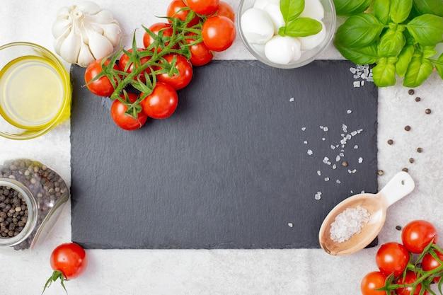 Ingredienti dell'insalata caprese italiana e tradizionale con pomodorini, mozzarella e basilico.
