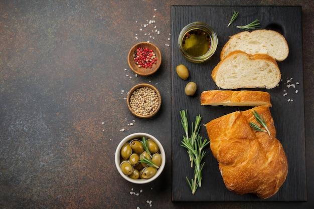 Pane ciabatta tradizionale italiano con olive, olio d'oliva, pepe e rosmarino su una superficie di pietra o cemento scuro