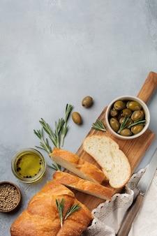 Pane ciabatta tradizionale italiano con olive, olio d'oliva, pepe e rosmarino su pietra grigio chiaro o superficie in cemento. messa a fuoco selettiva vista dall'alto.