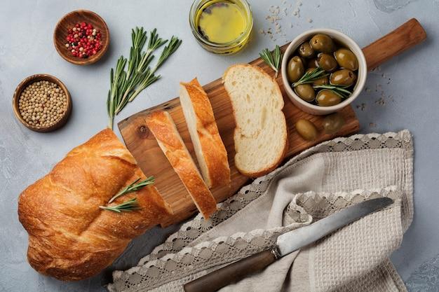 Pane ciabatta tradizionale italiano con olive, olio d'oliva, pepe e rosmarino su pietra grigio chiaro o superficie in cemento