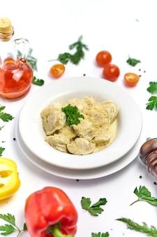 Pasta italiana tradizionale dei ravioli con carne o pesce storione su bianco