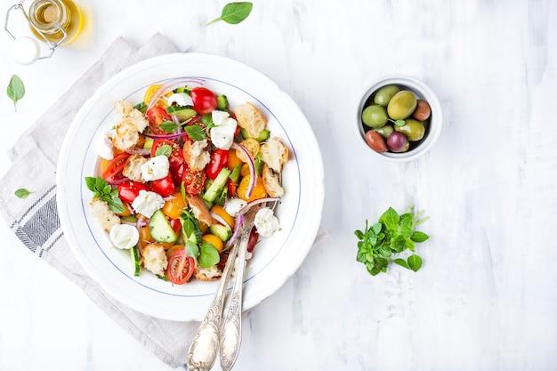 Panzanella di insalata tradizionale italiana con pomodori freschi e pane su sfondo chiaro