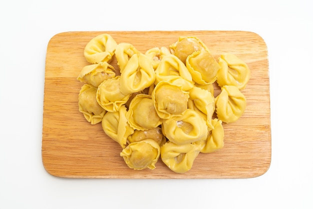 Pasta italiana tradizionale dei tortellini isolata sulla superficie bianca