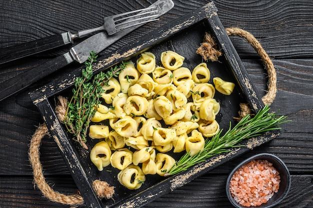 Pasta italiana tradizionale dei tortellini con gli spinaci in un vassoio di legno