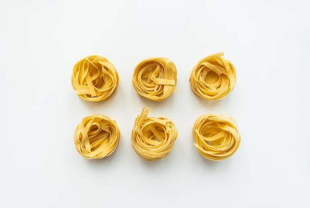 Tagliatelle di pasta di grano italiano isolato su priorità bassa bianca. vista dall'alto