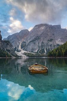 Italia. dolomiti e una barca nel lago di braes, paesaggio autunnale, verticale.