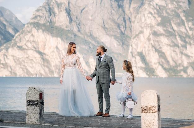 Italia, lago di garda. bella famiglia sulle rive del lago di garda in italia ai piedi delle alpi. padre, madre e figlia in italia