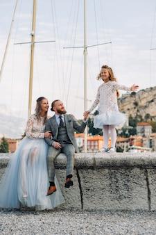 Italia, lago di garda. bella famiglia sulle rive del lago di garda in italia ai piedi delle alpi. padre, madre e figlia in italia.