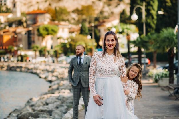 Italia, lago di garda. bella famiglia sulle rive del lago di garda in italia, ai piedi delle alpi. padre, madre e figlia in italia.