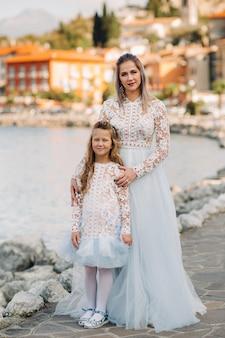 L'italia, il lago di garda.stylish madre e figlia sulle rive del lago di garda in italia ai piedi delle alpi. madre e figlia in italia