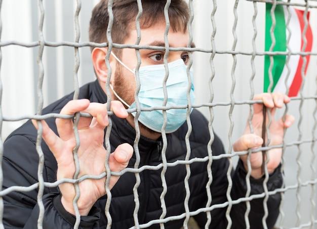 Quarantena italiana, stop coronavirus. focolaio di diffusione di coronavirus in italia. covid-19 in europa ue. uomo in maschera protettiva medica con bandiera italiana in gabbia